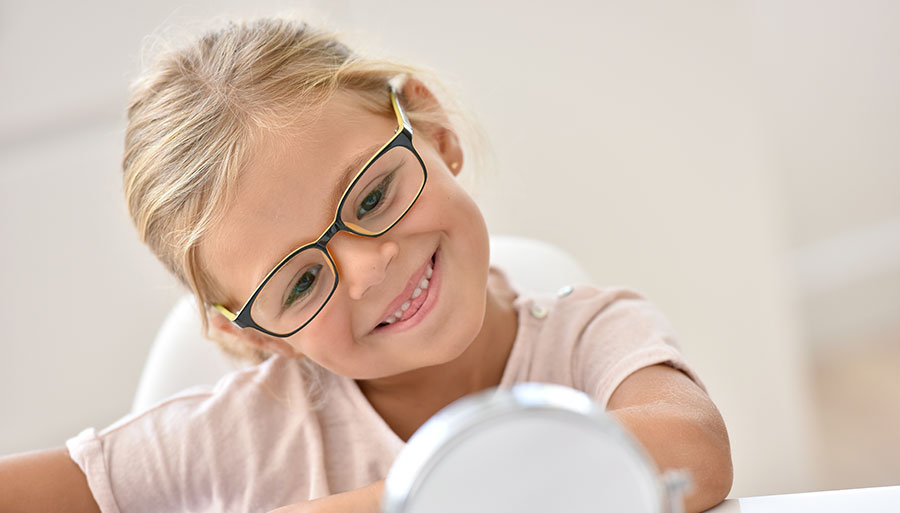 Child eyewear pediatric girl trying on glasses and smiling
